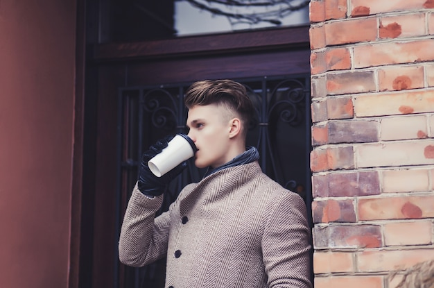 Erfolgreicher junger mann mit einem mantel, der heißen kaffee in der stadt trinkt