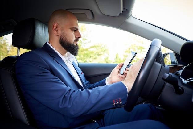 Erfolgreicher junger mann mit einem telefon in einem auto.