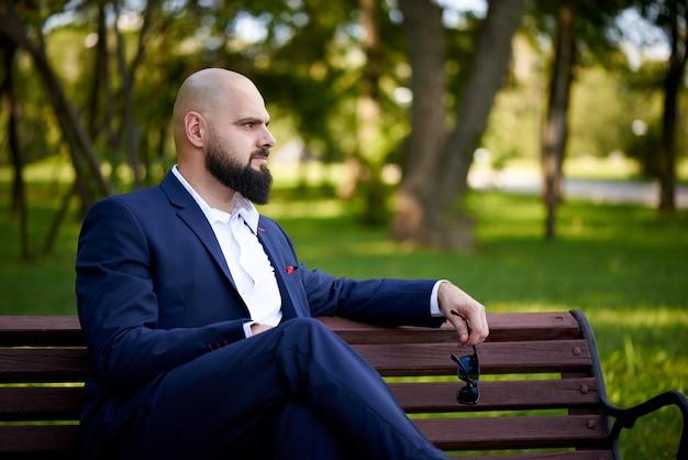 Erfolgreicher junger mann sitzt auf einer bank in einem park.