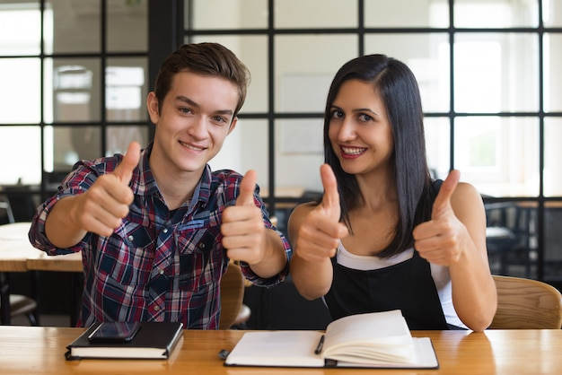 Erfolgreicher junger studentenjunge und -mädchen, die sich daumen zeigen