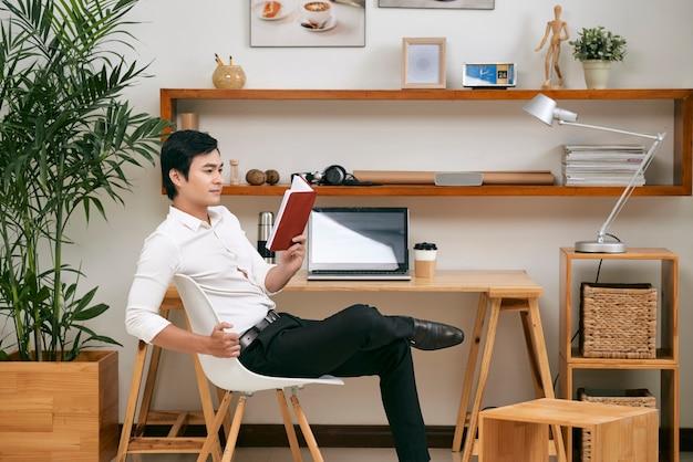 Erfolgreicher junger vietnamesischer unternehmer, der auf stuhl am schreibtisch sitzt und planer prüft