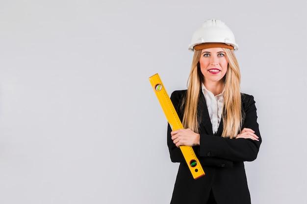 Erfolgreicher junger weiblicher architekt, der gegen grauen hintergrund steht