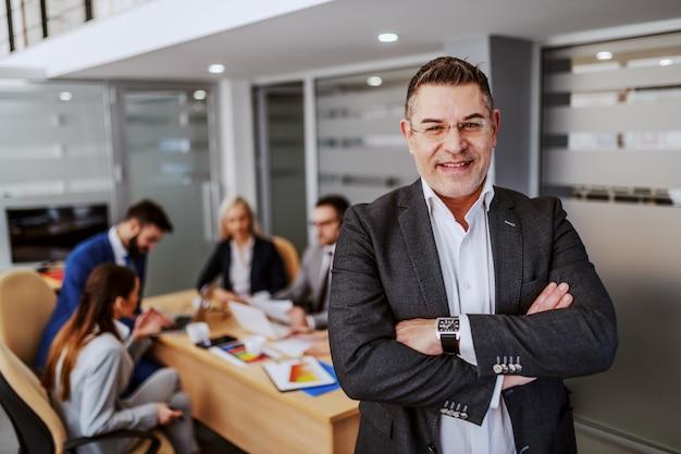 Erfolgreicher kaukasischer ceo mittleren alters, der im sitzungssaal mit gekreuzten händen steht und kamera betrachtet. im hintergrund arbeiten seine mitarbeiter an einem projekt für einen wichtigen kunden.