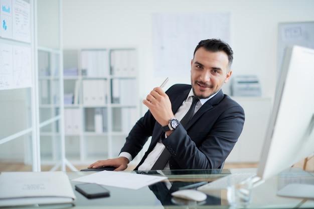 Erfolgreicher kaukasischer geschäftsmann, der am schreibtisch im büro und im lächeln sitzt