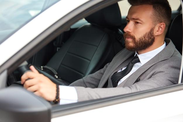 Erfolgreicher kaukasischer mann im formellen anzug, der ein auto fährt