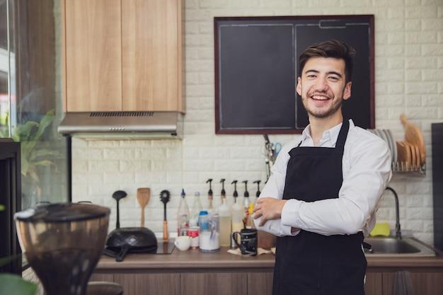 Erfolgreicher kleinunternehmerinhaber, der mit den gekreuzten armen in der kaffeestube steht