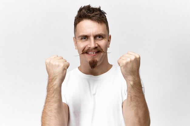 Erfolgreicher kreativer manager mit spitzbart und schnurrbart, der isoliert die fäuste zusammenhält und breit lächelt, aufgeregt und stolz auf unerwartete beförderung bei der arbeit oder gehaltserhöhung