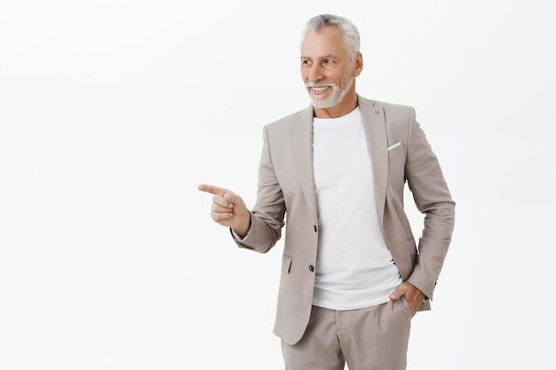 Erfolgreicher lächelnder geschäftsmann, der finger links zeigt