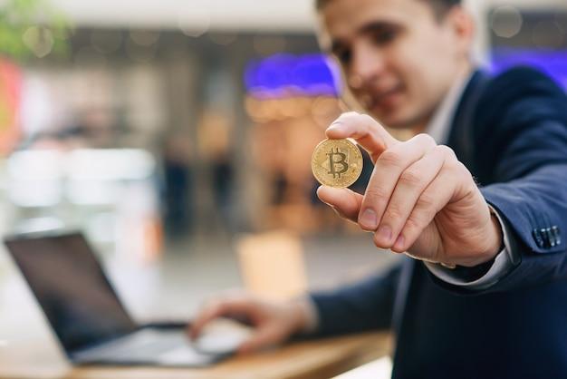 Erfolgreicher lächelnder geschäftsmann hält eine goldene bitcoin-münze in der hand