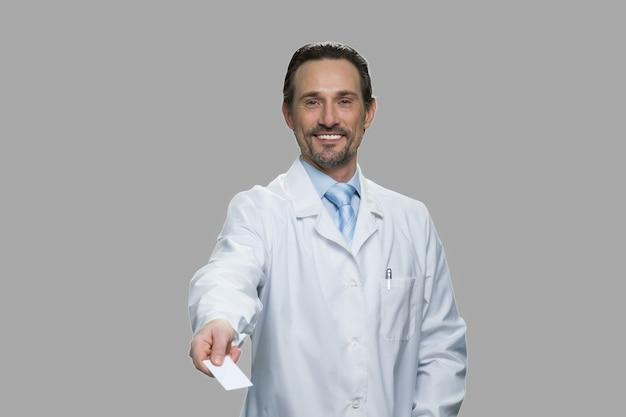 Erfolgreicher männlicher arzt, der visitenkarte anbietet. lächelnder mann im weißen mantel, der visitenkarte über grauen hintergrund übergibt.