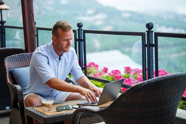 Erfolgreicher männlicher geschäftsmann, der im urlaub hinter einem laptop mit bergblick arbeitet. online-manager-workflow. arbeiten im freien mit schöner aussicht vom balkon