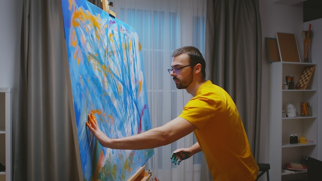 Erfolgreicher maler, der mit seinen händen ein meisterwerk der ölmalerei im kunststudio erstellt.