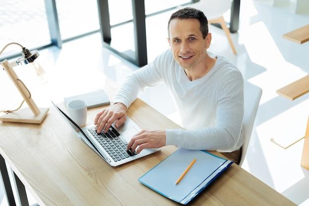 Erfolgreicher manager. attraktiver, glücklicher, kluger mann, der sie ansieht und bei der arbeit am laptop gute laune hat
