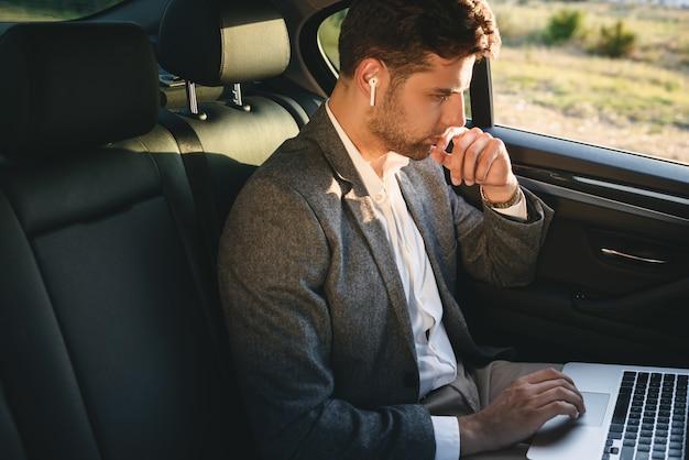 Erfolgreicher mann, der anzug und bluetooth-kopfhörer trägt, die auf laptop arbeiten, während zurück im geschäftsklassenauto sitzen