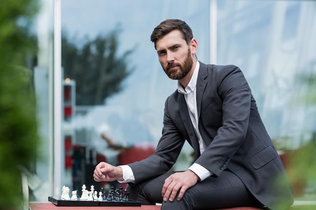 Erfolgreicher mann, der auf einer bank in einem business-anzug sitzt und schach spielt und nachdenklich in die kamera schaut