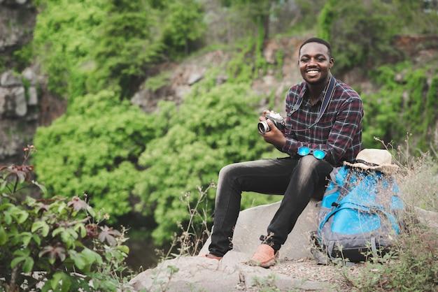 Erfolgreicher mann, der mit rucksack auf der klippe reist und sitzt