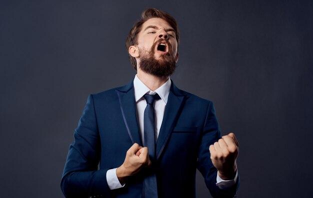 Erfolgreicher mann erfreut gefühle grauer hintergrund-anzug
