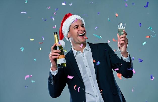 Erfolgreicher mann in einer jacke mit einer flasche champagner und einem glas feiert neujahr. studiofoto auf grauem hintergrund mit konfetti.