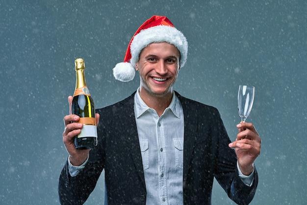 Erfolgreicher mann in jacke und weihnachtsmütze mit einer flasche champagner feiert neujahr. studiofoto auf grauem hintergrund.