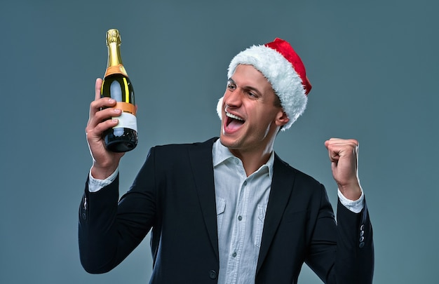 Erfolgreicher mann in jacke und weihnachtsmütze mit einer flasche champagner feiert neujahr und sagt ja. studiofoto auf grauem hintergrund.