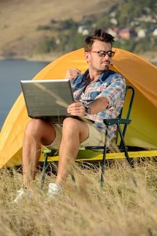 Erfolgreicher mann mit dem laptop, der im klappstuhl sitzt.