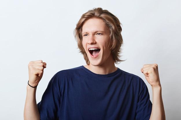Erfolgreicher mann mit fröhlichem ausdruck, geballte fäuste mit triumph, der sich über seinen erfolg bei der arbeit freut. glücklicher männlicher student, der froh ist, prüfungen erfolgreich zu bestehen. menschen, glück und freude konzept