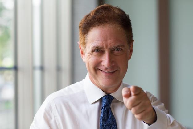 Erfolgreicher mann zeigt auf kamera mit dem finger