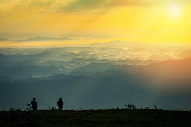 Erfolgreicher mannwanderer auf spitzenberg - mann, der auf hügel mit sonnenaufgang steht