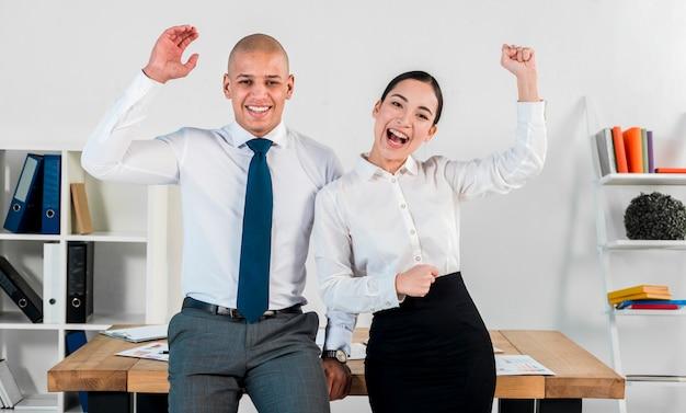 Erfolgreicher multi ethnischer junger geschäftsmann und geschäftsfrau, die am arbeitsplatz zujubelt