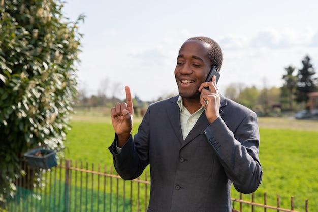 Erfolgreicher positiver afroamerikanischer geschäftsmann telefoniert mit einem kunden.