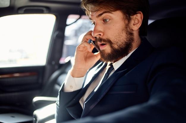 Erfolgreicher reicher mann in einem anzug, der am telefon spricht, während er einen personenwagen fährt