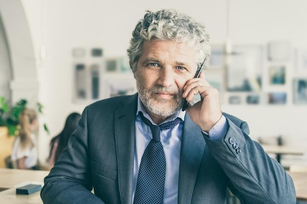 Erfolgreicher reifer geschäftsmann, der auf mobiltelefon spricht, bei der zusammenarbeit steht und sich auf schreibtisch schreibt
