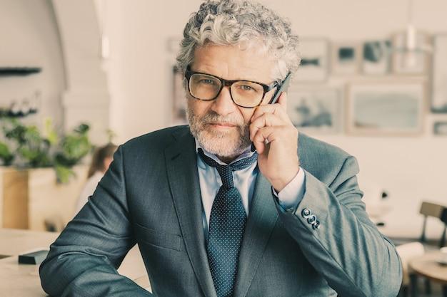 Erfolgreicher reifer geschäftsmann, der brille trägt und auf handy auf dem schreibtisch spricht