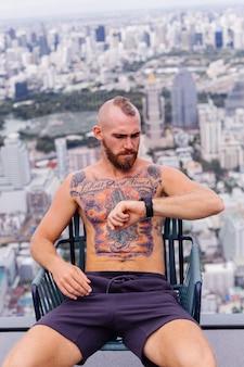 Erfolgreicher schöner europäischer bärtiger brutaler tätowierter starker mann oben ohne mit uhr sitzt auf stuhl auf hohem stockwerk mit erstaunlichem stadtblick