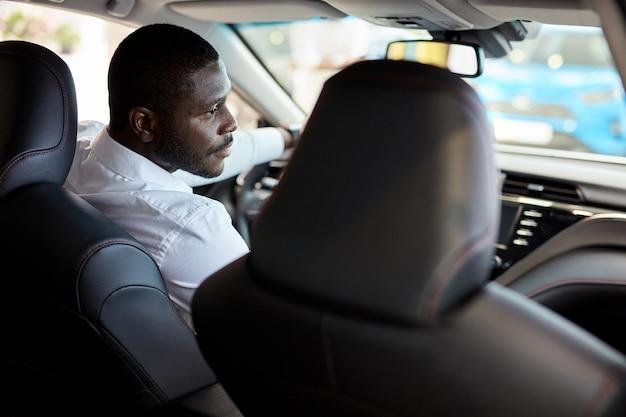 Erfolgreicher selbstbewusster geschäftsmann sitzt am steuer eines neuen automobils