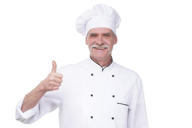 Erfolgreicher seniorenkoch mit handgeste