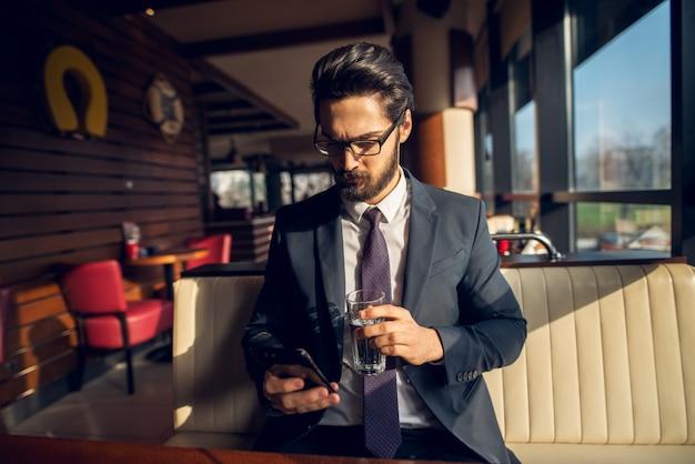 Erfolgreicher stilvoller fokussierter hübscher bärtiger geschäftsmann im anzug, der ein handy betrachtet, während er ein glas wasser in einem café oder restaurant hält.