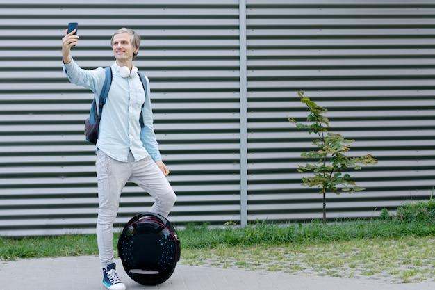 Erfolgreicher student-freiberuflerunternehmer des modernen jungen mannes des männlichen mannes mit rucksack und smartphone, die selfie mit futuristischem öko-elektromobil- / ausgleichsrad / elektrischem einrad im freien tun