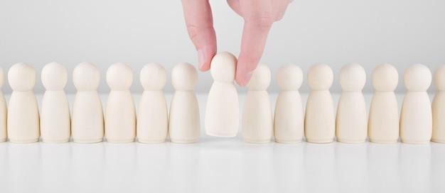 Erfolgreicher teamleiter. geschäftsmannhand wählt leute aus, die sich von der menge abheben. personal- und ceo-konzept