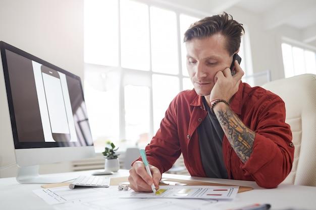 Erfolgreicher unternehmer, der im büro telefonisch spricht