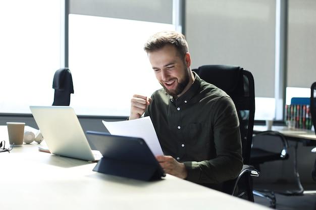 Erfolgreicher unternehmer studiert dokumente mit aufmerksamem und konzentriertem blick.