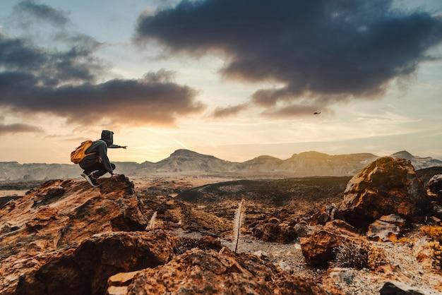 Erfolgreicher wanderer, der auf sonnenaufgang-berggipfel wandert, der zum himmel zeigt
