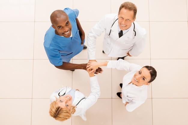 Erfolgreiches ärzteteam. draufsicht des selbstbewussten ärzteteams, das ihre hände zusammenhält und lächelt