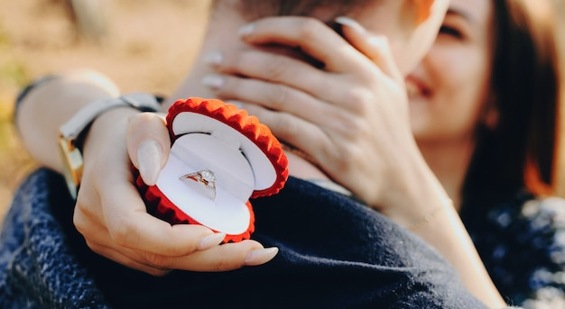 Erfolgreiches bitten um die heirat eines kaukasischen mannes mit roter ringbox, die von seiner zukünftigen frau umarmt wird