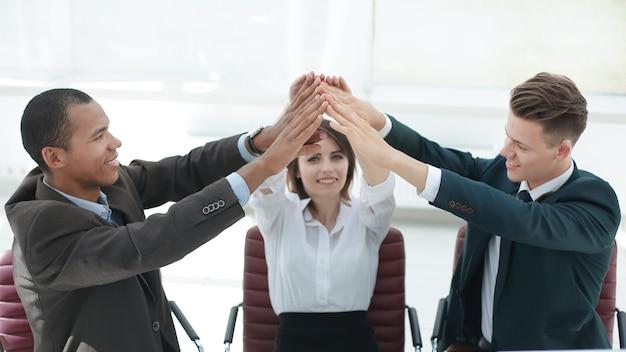 Erfolgreiches business-team, das high five gibt und hinter einem schreibtisch sitzt