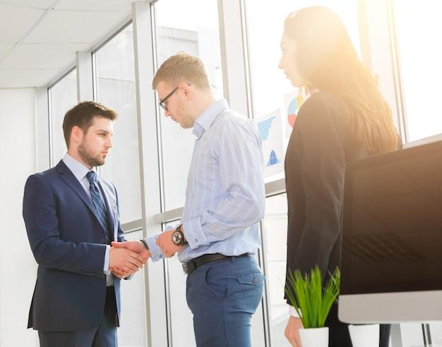 Erfolgreiches business-team, das im büro die hand schüttelt