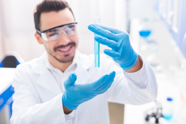 Erfolgreiches experiment. selektiver fokus der männlichen hand getragenen phiole mit flüssigkeit gefüllt und mann aufsetzen schutzbrille und grinsend
