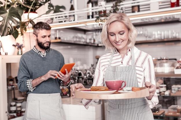 Erfolgreiches geschäft. glückliche freudige frau, die in einer guten stimmung ist, während sie die bestellung zu den café-kunden bringt