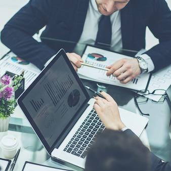 Erfolgreiches geschäftsteam am arbeitsplatz, das die marketingberichte bespricht.