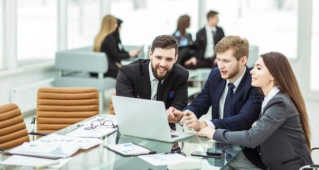 Erfolgreiches geschäftsteam, das am laptop arbeitet und den aktuellen finanzbericht erstellt